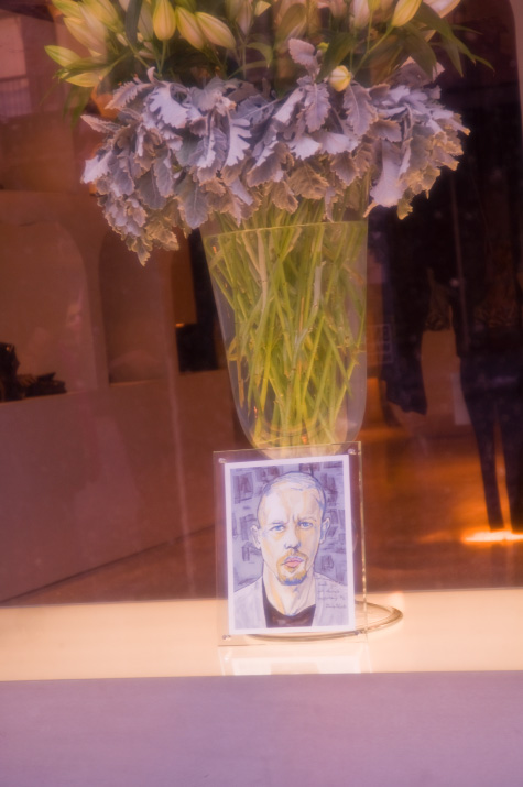 A picture close up picture of Danny Roberts tribute painting of Lee Alexander McQueen in the McQueen Store in New York City with a flow vase