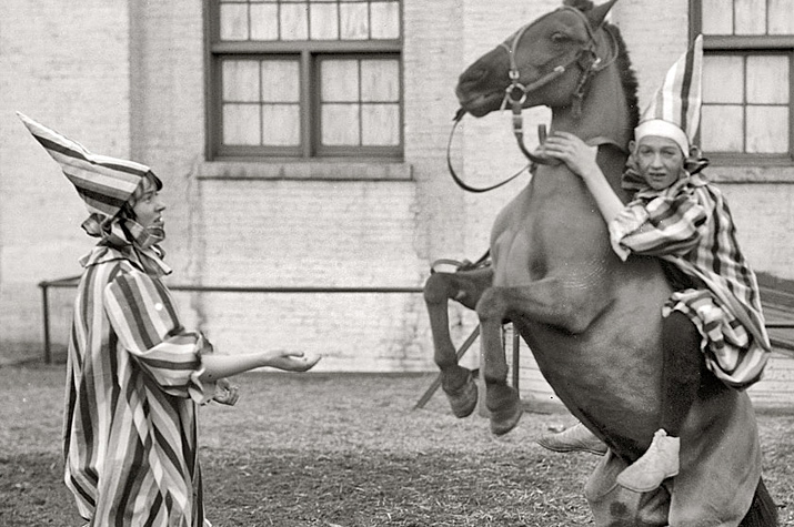 Inspirational image 1900 - 1920 black and white picture of two boys dressed as clowns one is on a horse and the horse is jumping and bucking the kid off