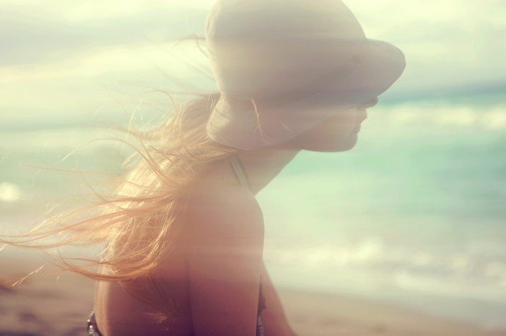 A warm Inspirational Photo of a Profile of a beautiful Girl wearing a hat and hair blowing with a soft focus by the ocean