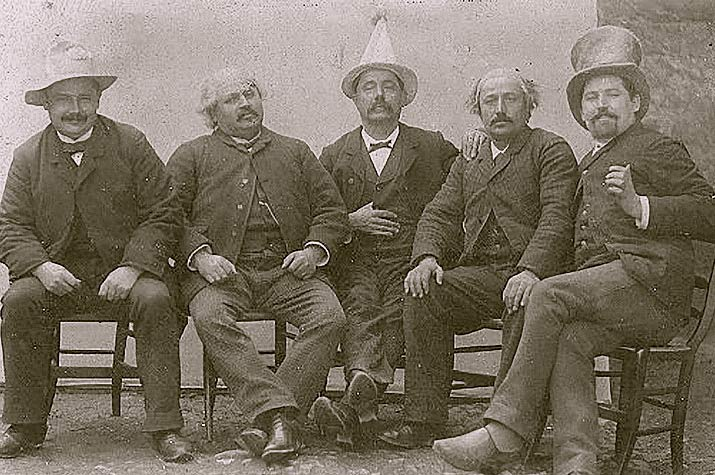 Old Photo From the 1800s Sepia of 5 sitting men on of the men has a funny pointed hat