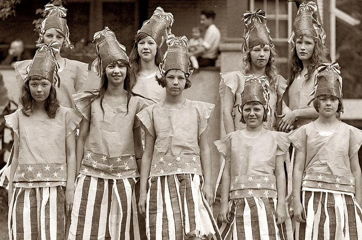 An Old Sepia Photo Archived Picture of 9 young girls standing in two rows for the 4th of july Wearing Big Hats and American Flage Skirts and shirts in the 1920s or 1940s or 1930s