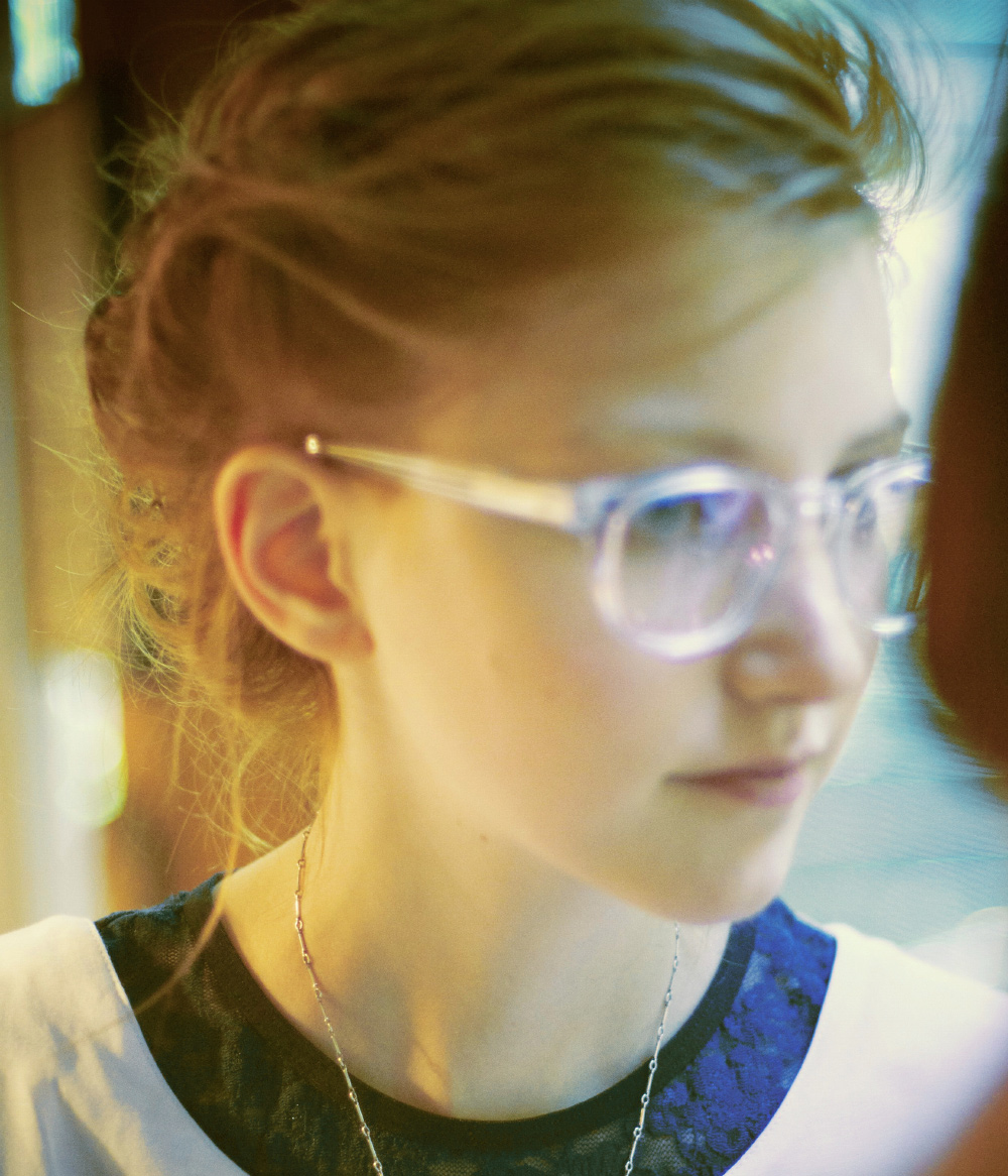 Semi out of focus Photo of bunny bisous Writer and Stylist and Red Head Julia Frakes from Next Model Management. She has clear glasses on and is wear a blue lace undershirt with a white dress on for Rachel Antonoff Spring 2011 Collection. Photo my Igor and andre Photography