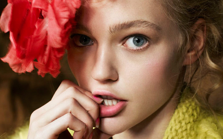 Igor and andre inspiration Friday Post of beautiful Russian Img Model Sasha Pivovarova looking cute red flower in hair hand in mouth yellow cardigan and blue eyes.