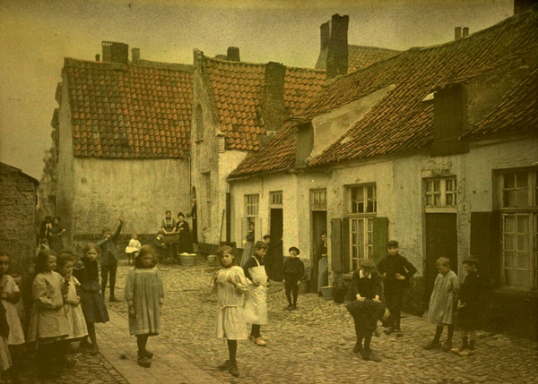 A sephia 1800s photo of kids in courtyard