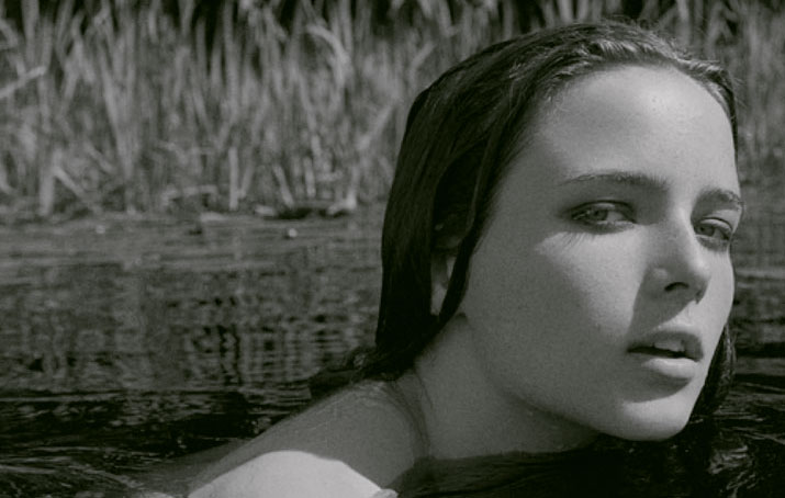 A Black and white photo of a girls head coming out of the water as she is swimming looking into the camera inspiration friday picture by jimmy backius