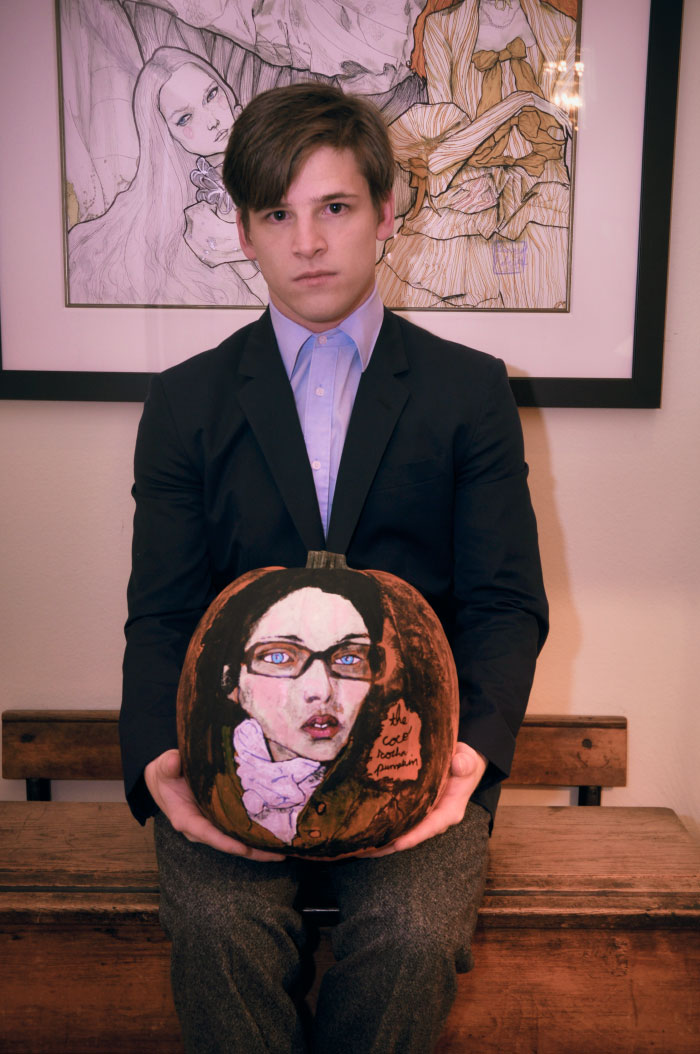 A portrait of Danny Roberts holding a pumpkin he painted of Model Coco Rocha
