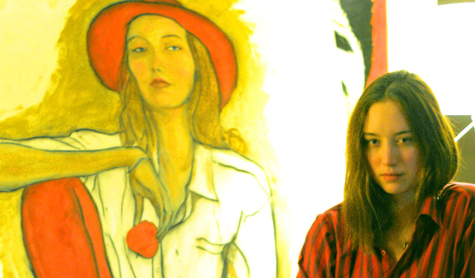 This is a Picture of Model Sophie Ward in front of Danny Roberts painting of her